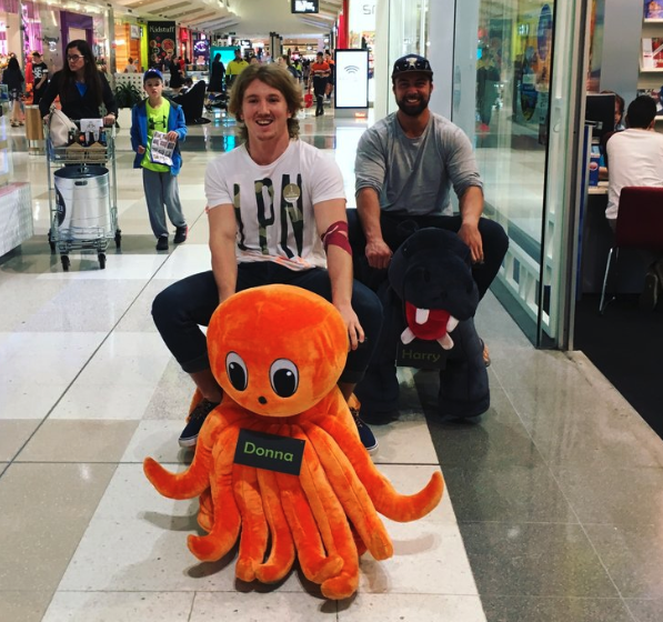 Daniel Bourke riding a stuff octopus through a shopping centre.