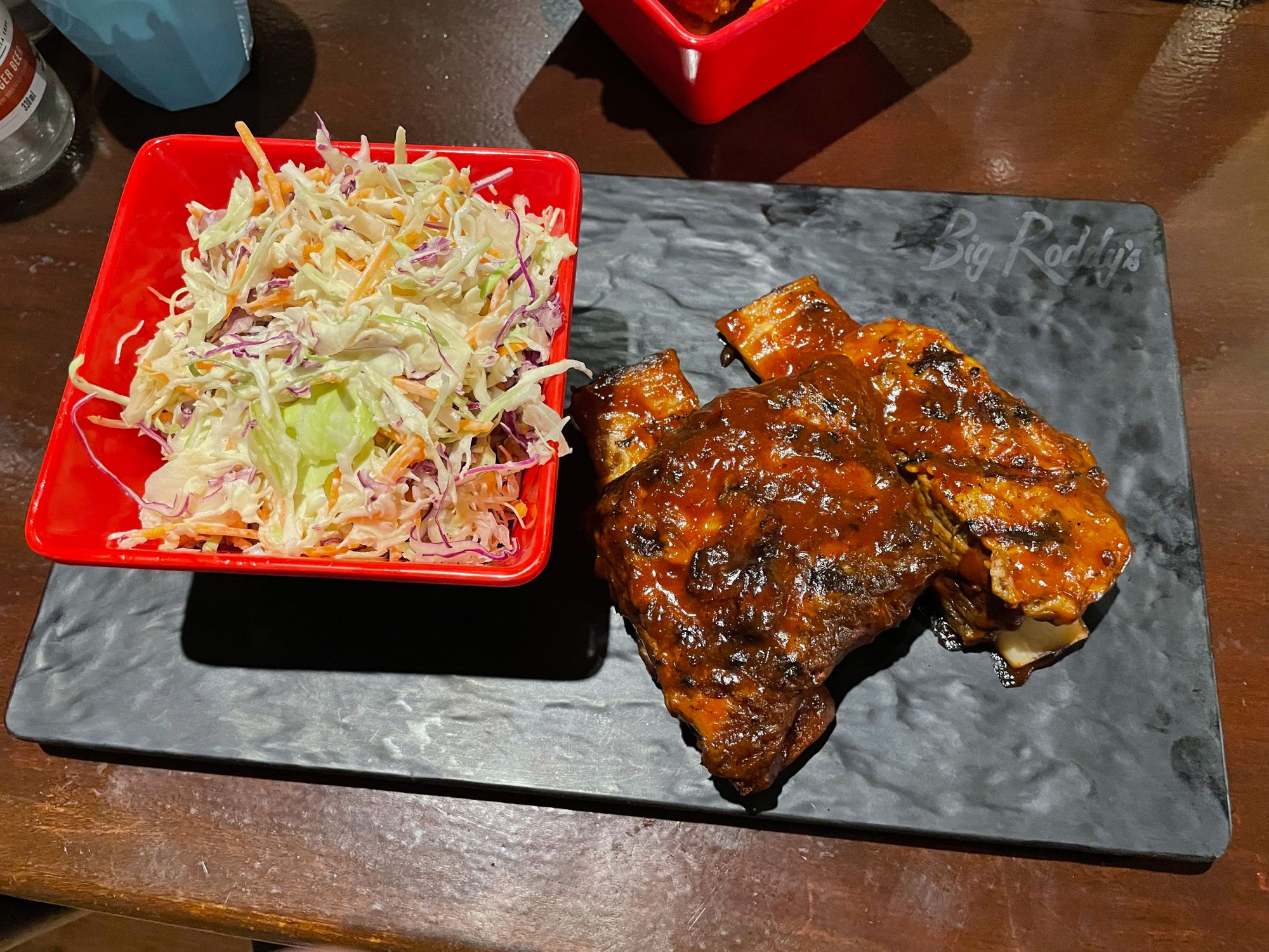 pork ribs with sauce and coleslaw on a rectangular plate from Big Roddy's